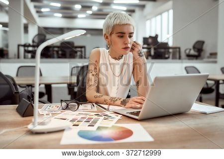 Young Stylish Tattooed Female Designer Working On New Project While Standing Near Office Desk. Focus