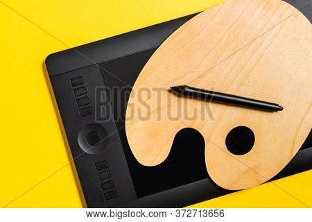 Top View Of Wooden Palette And Graphics Tablet With Stylus On Yellow Surface