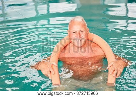 Happy senior man with buoyancy aid doing aqua fitness in rehab