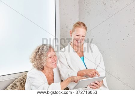 Senior women using tablet computer at spa hotel on a wellness trip
