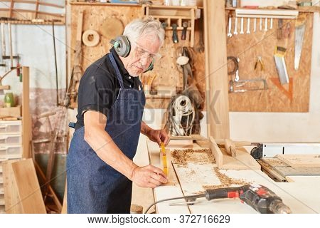 Carpenter master while measuring with the folding rule at the workbench of his workshop