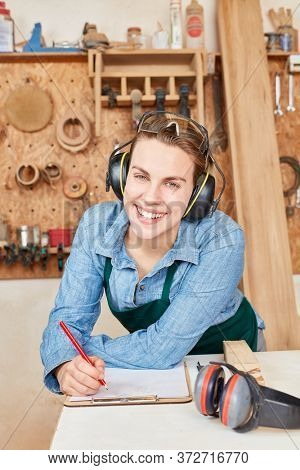 Happy young woman as a carpenter or joiner trainee in a joiner's workshop