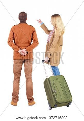 young couple in winter jacket traveling with suitcas. Back view. Rear view people collection. backside view of person. Isolated over white background.