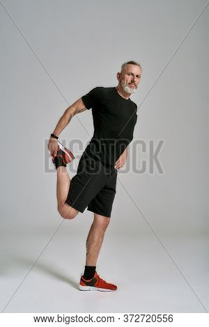 Full Length Shot Of Middle Aged Muscular Man In Black Sportswear Looking At Camera While Stretching