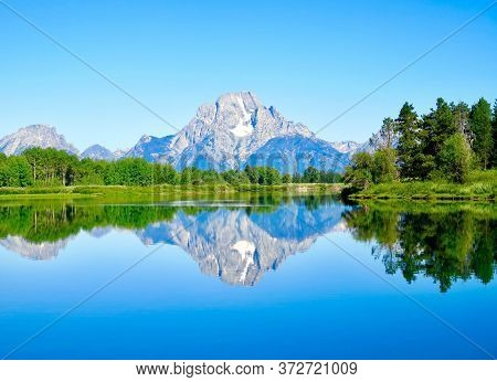 A Picturesque Lake And Large Mountain Hills.