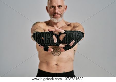 Half Naked Middle Aged Athletic Man, Kickboxer Stretching Hands Standing In Studio Over Grey Backgro