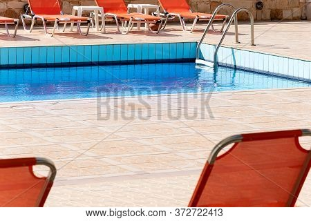 Swimming Pool With Empty Sunbeds Outside Of Vacation Hotel. Contemporary Relax Blue Water Pool  Phot
