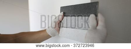 Male Builder Selects Color For Painting Putty Wall. Choose Color For Room. Plastering Flat Surfaces.
