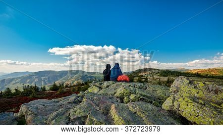 Two Tourist Sitting On A Rock And Watching Colorful Treeless Mountain Landscape, Jeseniky, Czech Rep