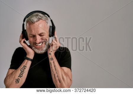 Middle Aged Muscular Man In Black T Shirt And Headphones Smiling While Listening To Music, Posing In