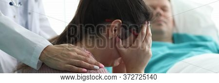 Woman In Clinic Crying Near Man In Hospital Bed. Unique Care System For Severe Patients. Care And Co