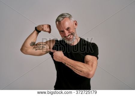 Look At This. Smiling Middle Aged Muscular Man In Black T Shirt Showing His Biceps, Tattoos While Po