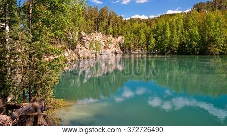 Beautiful View On Clear Cyan Lake With Sandstone Rocks In Colorful Yellow Green Forest In The Backgr