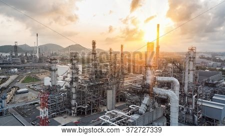 Aerial View Of Chemical Oil Refinery Plant, Power Plant And Metal Pipe On Sunrise Sky Background.