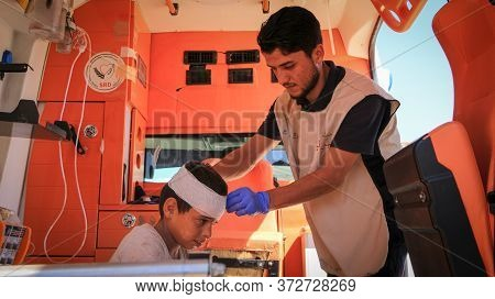 Aleppo, Syria 12 April 2020 A Nurse Embraces A Child And Treating Him Inside The Ambulance