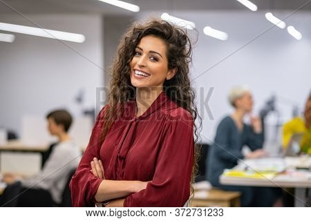 Successful businesswoman standing in creative office and looking at camera while smiling. Portrait of beautiful business woman standing in front of business team at modern agency with copy space.