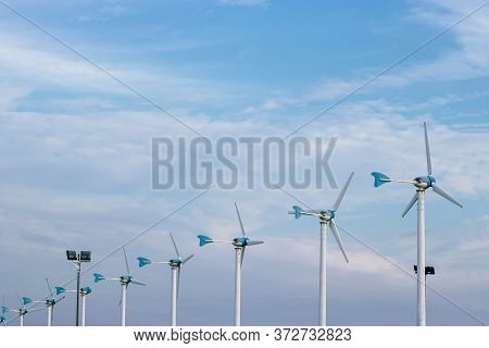 Windmills Electricity And Bright Blue Sky With Fluffy White Clouds. Renewable Energy. Sustainable El