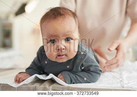Close Up Portrait Of Cute Mixed-race Baby Looking At Camera While Lying On Changing Table With Blurr