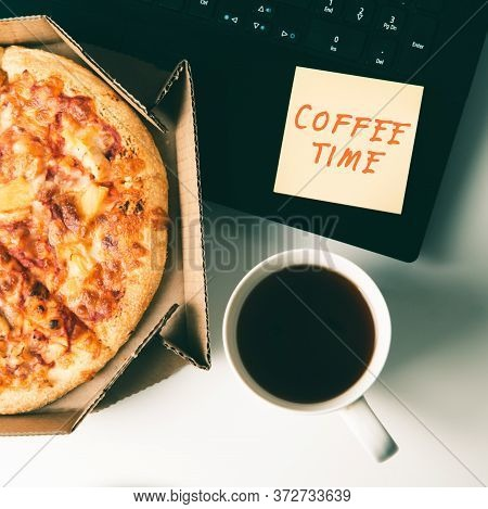 Pizza In Box, Cup Of Coffee, Laptop And Sticker With Text Coffee Time On Desk In Office. Concept Of