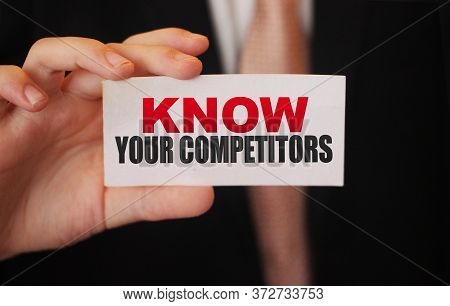 Businessman Putting A Card With Text Know Your Competitors. Business Concept