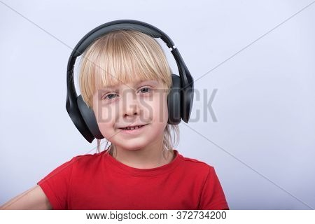 Portrait Of Fair-haired Boy In Headphones On White Background Closeup