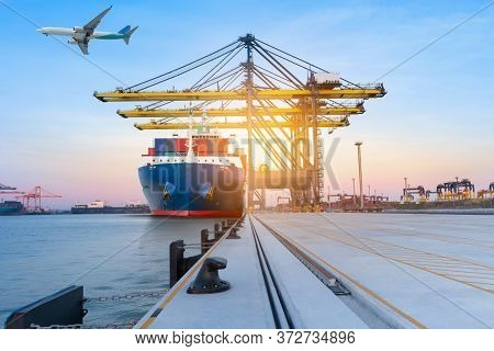 Cargo Container Ship Under The Crane In The International Yard Port For Loading Big Tank From Ship T