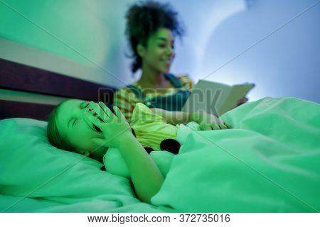 African American Woman Baby Sitter Reading Book To Cute Little Girl In The Evening. Nanny Holding Bo