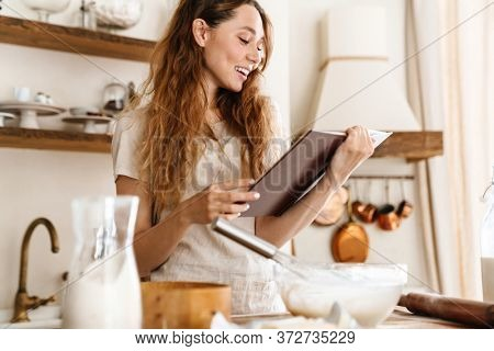 Attractive young cheerful girl baking at the kitchen, making dough, holding recipe book, having ideas