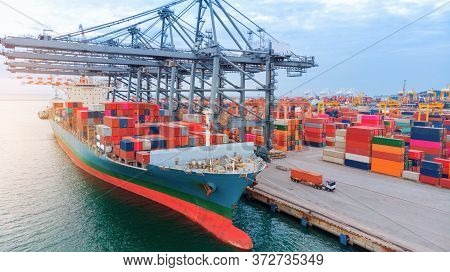 Aerial Of Cargo Container Ship Carrying Container  Under Big Crane Loading Cargo Import And Export S