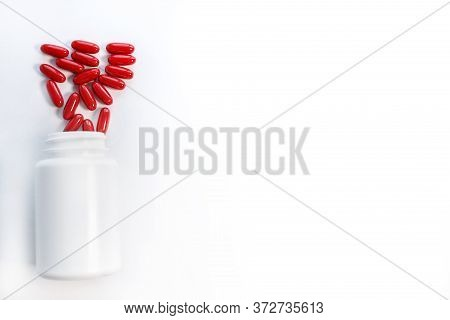 Closeup Red Pills And Pill Bottle, Isolated Over White.pills And Pill Bottle On White Background.