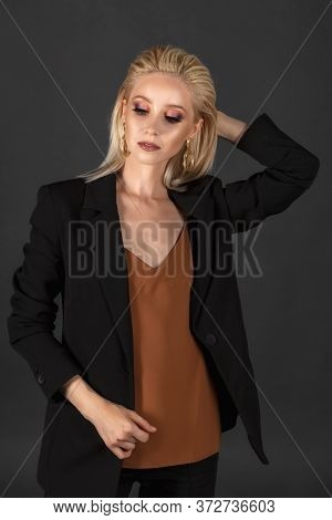 Beautiful Girl With Long Blond Hair In An Elegant Black Suit Against The Dark Gray Background. Hairs