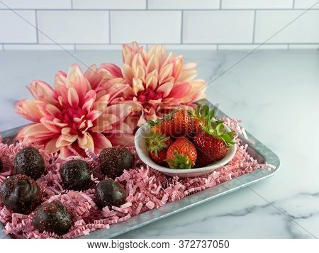 Chocolate Covered Strawberry Cake Balls Arranged On A Metal Tray With Pink Paper Shreds, A White Bow