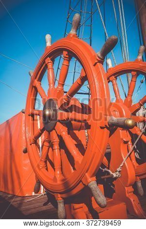 Red Wooden Wheel Helm On Antique Ship