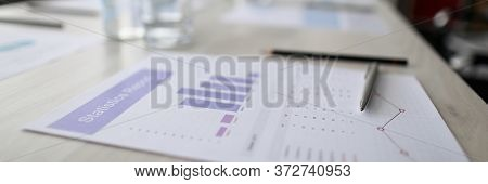 Close-up Of Statistics Paper And Silver Pen Laying On Office Desktop. Analyzing And Gathering Statis