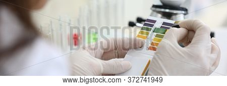 Close-up Of Scientists Hands Comparing Test Colors With Samples. Chemist Making Experiment In Labora