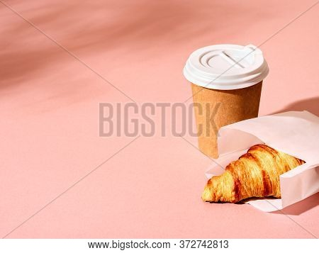 Coffee In A Craft Paper Cup And Croissant On Pink Background With  Foliage Shadow. Sunny Urban Scene
