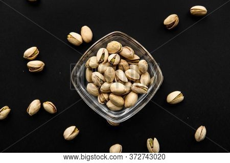 Pistachios In A Small Plate With Scattered Nuts Of Almonds Around A Plate On A Black Surface. Pistac