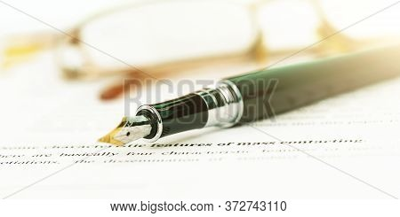 Vintage Black Fountain Pen With Golden Quill Lies Against Blurry Glasses On Table Extreme Close View
