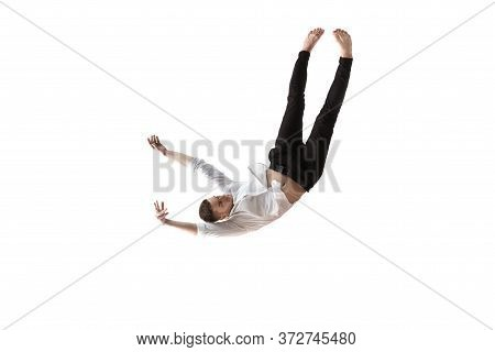 Mid-air Beauty Cought In Moment. Full Length Shot Of Young Man Hovering In Air And Keeping Eyes Clos