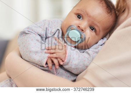Close Up Portrait Of Cute Mixed-race Baby Sucking On Pacifier While Laying In Mothers Arms, Copy Spa