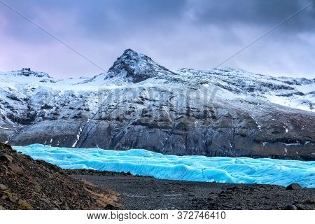Snow couvered mountain and blue glacial ice for the Svinafellsjokul glacier in southeast Iceland. This is the largest ice cap in Europe.