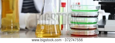 Close-up Of Assistant Hands Pouring Yellow Liquid Into Flask. Professional Scientist Making Mixture