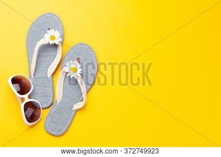 Summer vacation items and accessories. Flip flops and sunglasses on yellow background. Top view flat lay with copy space