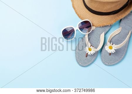 Summer vacation items and accessories. Flip flops, sunglasses and sun hat on blue background. Top view flat lay with copy space