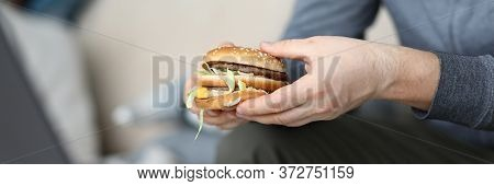 Focus On Male Hand Holding Unhealthy Sandwich And Preparing To Consume Fat Dish Full Of Quick Carboh