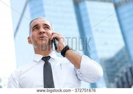 Stock Trader, Investor, Businessman Talking On The Mobile Phone As Worried About Trade War News And