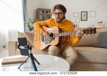 Young bearded musician or music teacher in casualwear sitting on couch in living-room and playing guitar in front of smartphone camera