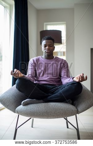 Peaceful Teenage Boy Meditating Sitting In Chair At Home