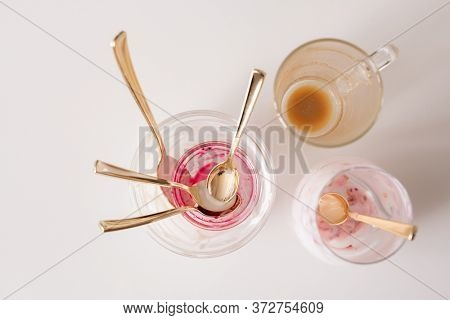Group of empty unwashed glasses and teaspoons on kitchen table after breakfast consisting of coffee and yoghurt with homemade jam