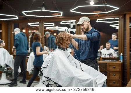 At Barbershop. Side View Of Young Stylish Redhead Guy Sitting In Barbershop Chair While Barber Dryin